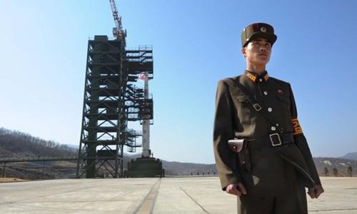 Một binh sĩ Triều Tiên đứng trước tên lửa Unha-3 tại bãi phóng Tongchang-ri. Ảnh: AFP.