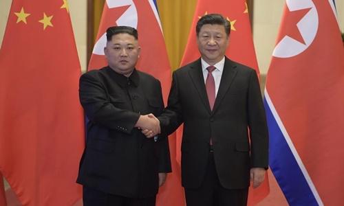 Chủ tịch Trung Quốc Tập Cận Bình (phải) bắt tay Chủ tịch Triều Tiên Kim Jong-un tại Bắc Kinh hôm 8/1. Ảnh: Xinhua.