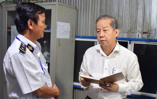 Ông Phan Ngọc Thọ (bìa phải) trao đổi với cán bộ kiểm dịch lúc 3h30 sáng 7/3. Ảnh: Ngọc Minh