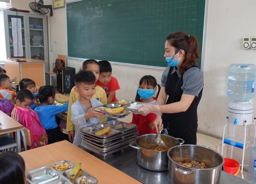 Học sinh lần lượt xếp hàng để nhận suất ăn tại lớp.