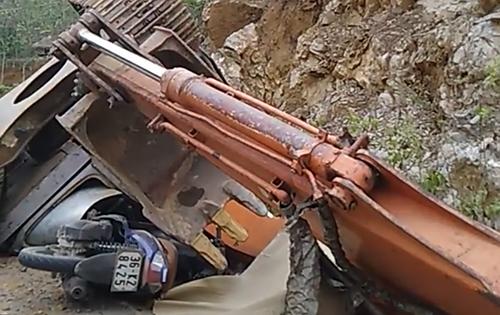 Xe máy và nạn nhân nằm dưới gầm máy xúc. Ảnh cắt từ clip.