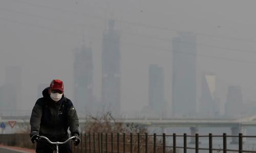 Một người đàn ông đeo khẩu trang đạp xe gần sông Hàn, thủ đô Seoul, Hàn Quốc. Ảnh: AP.