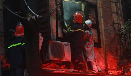 Lực lượng cứu hỏa phun nước dập tắt đám cháy. Ảnh: Tất Định