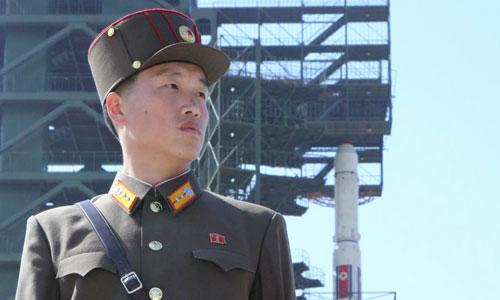 Binh sĩ Triều Tiên đứng gác cạnh tên lửa Unha-3 đưa vệ tinh lên vũ trụ ở cơ sở Sohae năm 2012. Ảnh: KCNA.