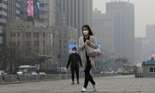 Người dân Hàn Quốc đeo khẩu trang ra đường vì ô nhiễm không khí nặng. Ảnh: AFP.