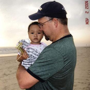 Ông Rob Shepherd bế Haven trên tại khi đứng trên bãi biển Đà Nẵng năm 2004. Ảnh: BBC.