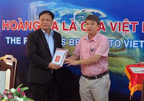 Ông Trần Đức Anh Sơn (bìa phải) chụp ảnh trong một lần tặng tài liệu chủ quyền biển đảo cho UBND huyện Hoàng Sa (Đà Năng). Ảnh: Báo Đà Nẵng.