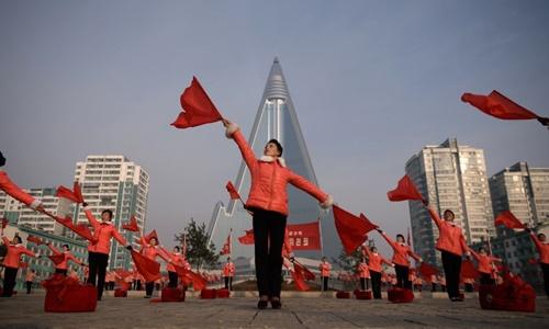 Màn múa cờ trước khách sạn Ryugyong ở Bình Nhưỡng ngày 9/3. Ảnh: AFP.