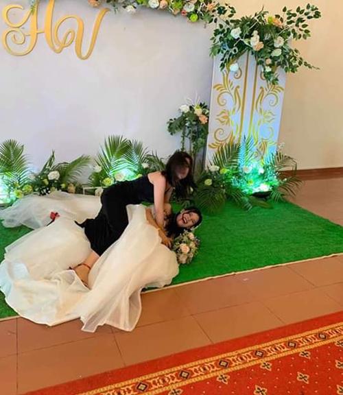 Người đẹp ôm chặt cô dâu khiến cả hai ngã xuống đất.