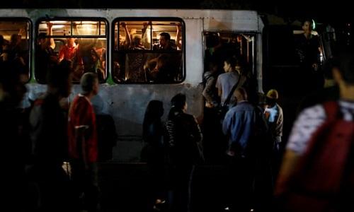 Người dân lên xe buýt trong lúc ngoài trời tối đen vì mất điện. Ảnh: Reuters.