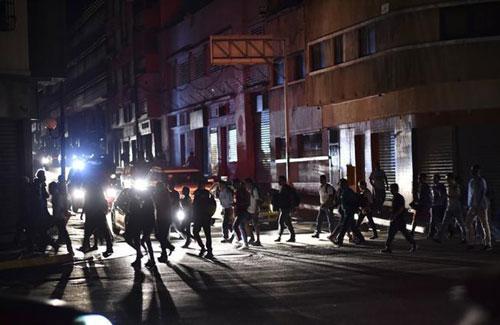 Người dân tại một trung tâm mua sắm ở thủ đô Caracas sau khi mất điện chiều qua. Ảnh: Reuters.