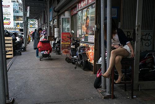 Một người phụ nữ ngồi bên ngoài tiệm massage chào mời khách ở khu Flushing, Queens, New York, Mỹ. Ảnh: NYT.