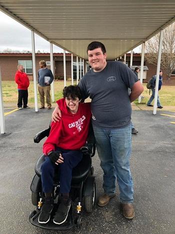Brandon hạnh phúc khi nhận món quà từ bạn thân là chiếc xe lăn chạy bằng điện. Ảnh:Caddo Hills School District
