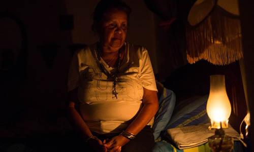 Một phụ nữ Venezuela dùng đèn dầu để thắp sáng ngôi nhà tại Caracas hôm 9/3. Ảnh: AFP.