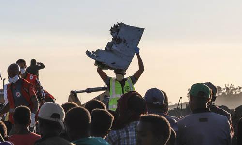 Nhân viên cứu hộ bê một mảnh vỡ của chiếc Boeing 737 MAX 8 tại hiện trường vụ tai nạn cách thủ đô Addis Ababa của Ethiopia khoảng 50 km hôm 10/3. Ảnh: AFP.
