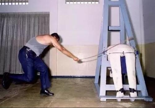 Cán bộ nhà tù luyện đánh roi trên người nộm.