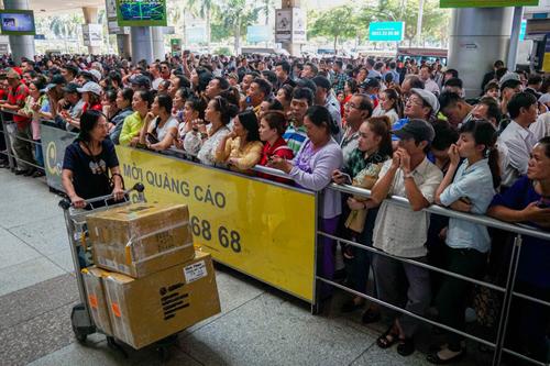 Hàng nghìn người đến đón người thân từ nước ngoài về quê ăn Tết cổ truyền vào trưa 24/1tại sảnh đón của ga quốc tế sân bay Tân Sơn Nhất. Ảnh: Quỳnh Trần