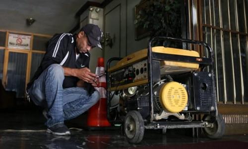Một người đàn ông sạc điện thoại cạnh máy phát điện ở Caracas hôm 11/3. Ảnh: AFP.