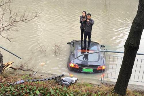 Ôtô Tesla lao xuống sông, hai người trong xe đứng lên nóc