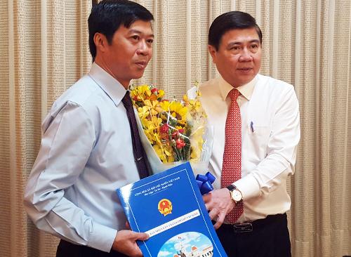 Chủ tịch UBND TP HCM Nguyễn Thành Phong trao quyết định bổ nhiệm Chánh văn phòng Đoàn ĐBQH và HĐND thành phố cho ông Trần Tuấn Ngọc (trái). Ảnh: Trung Sơn