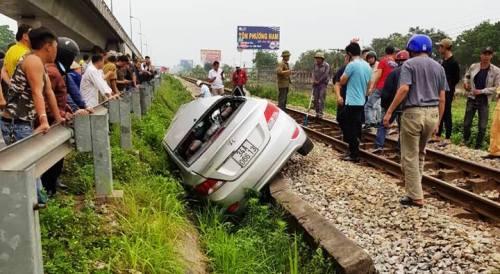 Ôtô gặp nạn được đẩy xuống rãnh nước cạnh đường ray để đoàn tàu tiếp tục lưu thông. Ảnh: CTV
