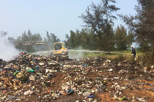 Nhân viên phun nước kết hợp san ủi để dập tắt đám cháy bãi rác. Ảnh: Hoàng Táo