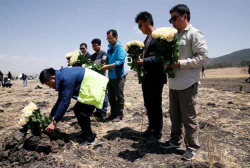 Một nhóm người Trung Quốc tưởng niệm đồng nghiệp thiệt mạng tại hiện trường vụ tai nạn máy bay gần thị trấn Bishoftu, Ethiopia. Ảnh: Reuters