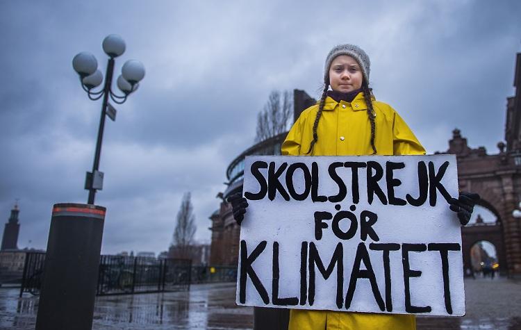 Greta Thunberg và tấm biển viết tay nổi tiếng. Ảnh: EPA