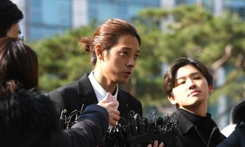 Ca sĩ Jung Joon-young (buộc tóc)đến sở cảnh sát ở Seoul ngày 14/3. Ảnh: AFP.
