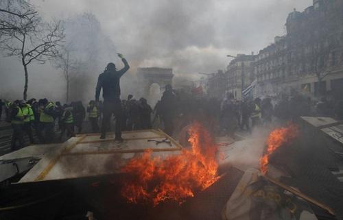 Người biểu tình áo vàng đốt phá tại Khải Hoàn Môn, Paris hôm 16/3. Ảnh: Reuters.