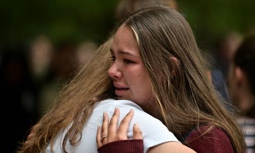 Hai sinh viên an ủi nhau trong lễ cầu nguyện ở Christchurch ngày 18/3. Ảnh: AFP.