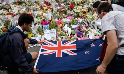 Sinh viên ngày 18/3 đặt cờ New Zealand bên cạnh nến và hoa trong lễ cầu nguyện cho nạn nhân vụ xả súng. Ảnh: AFP.