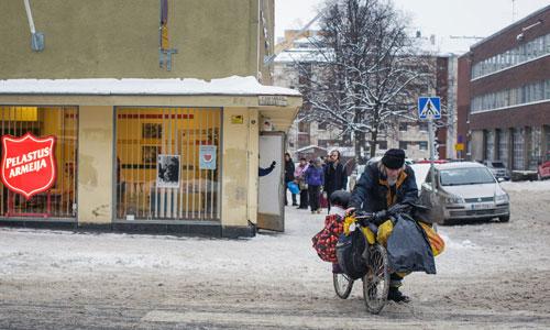 Cụ già đẩy xe đạp rời khỏi khu nhà ở xã hội Đội quân Cứu thế ở thủ đô Helsinki của Phần Lan. Ảnh: Huffington Post.