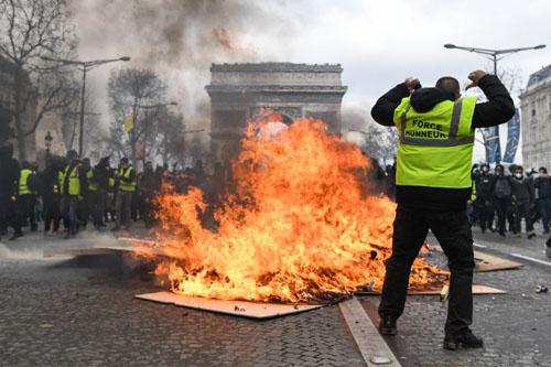 Người biểu tình Áo vàng đốt phá trước Khải Hoàn Môn, Paris hôm 16/3. Ảnh: AFP.