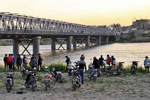 Người dân và thân nhân của các nạn nhântập trung bên bờ sông Tigrissauvụ chìm phàngày 21/3. Ảnh: AP