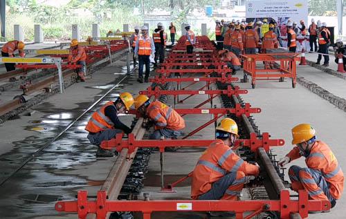 Các kỹ sư và công nhân lắp ray tại Depot Nhổn sáng 31/1. Ảnh: Võ Hải.