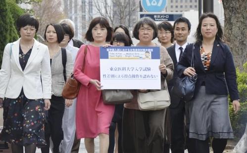 Tập thể nữ nguyên đơn và luật sư tiến về tòa án sơ thẩm Tokyo. Ảnh: KYODO.