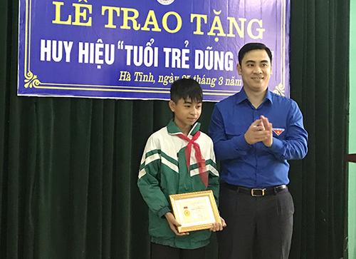 Em Nguyễn Văn Chương nhận huy hiệu Tuổi trẻ dũng cảm từ đại diện Tỉnh đoàn Hà Tĩnh. Ảnh:Đức Hùng
