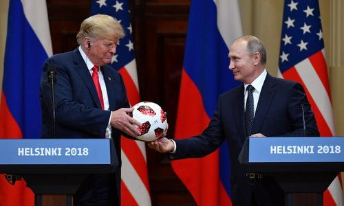 Tổng thống Trump (trái) nhận quả bóng từ Tổng thống Putin tại Helsinki. Ảnh:Reuters.