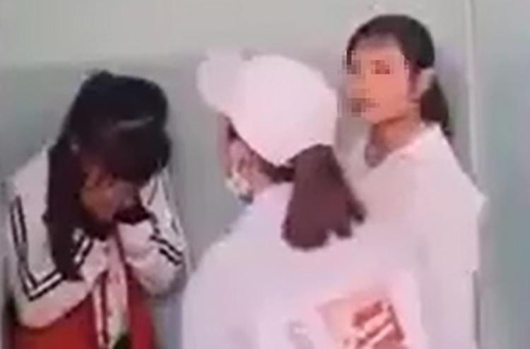 Nữ sinh lớp 7 (trái) ở Phú Yên bị nhóm đàn chị cùng trường vâyđánh trong nhà vệ sinh, hôm 15/3. Ảnh: Cắt từ video