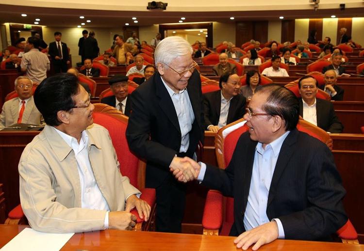 Tổng bí thư Nguyễn Phú Trọng bắt taynguyên Tổng bí thư Nông Đức Mạnh (bên phải) và nguyên Thủ tướng Nguyễn Tấn Dũng. Ảnh: TTX
