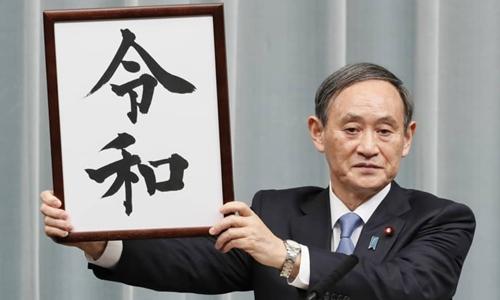 Chánh văn phòng nội các Yoshi Suga giơ tấm biển viết chữ Reiwa, niên hiệu triều đại mới của Nhật Bản, tại văn phòng thủ tướng sáng nay ở Tokyo. Ảnh: Kyodo.
