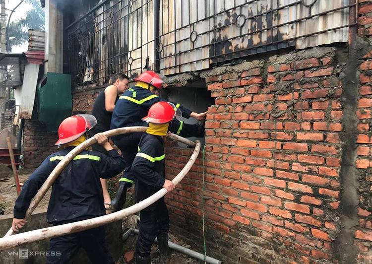 Cảnh sát đập tường tiếp cận đám cháy. Ảnh: Gia Chính.