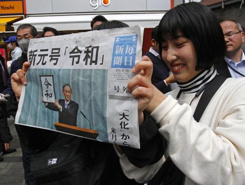 Một người phụ nữ cầm trên tay tờ báo Mainichi Shimbun đưa tin về niên hiệu mới của Nhật Bản. Ảnh: AP.