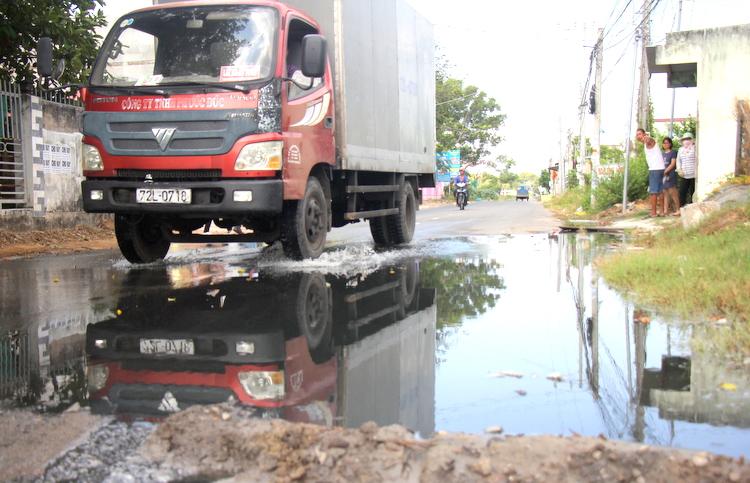 Nước thải chảy tràn trên con đường liên xã. Ảnh: Nguyễn Khoa.