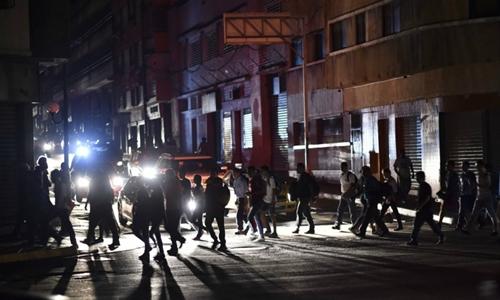 Người dân băng qua khu phố mất điện ở thủ đô Caracas hôm 8/3. Ảnh: AFP.