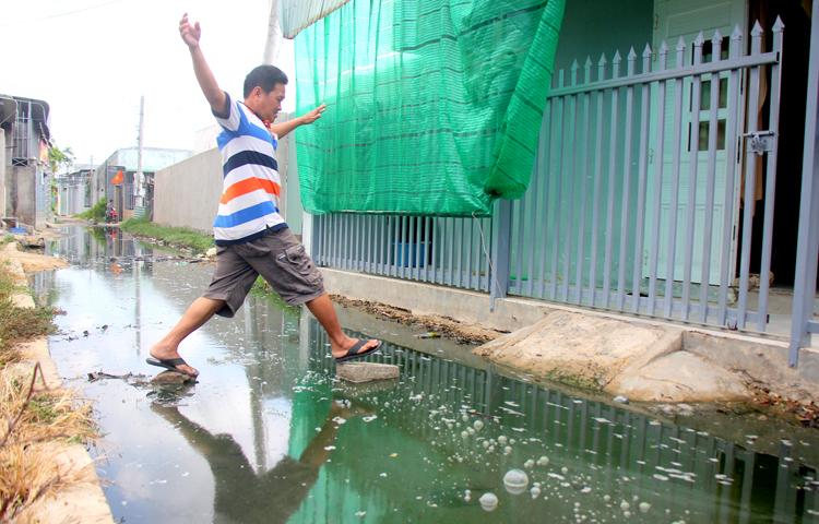 Con hẻm bị nước thối tràn vào khiến cuộc sống của người hai xã giáp ranh Phước Hưng và Phước Tỉnhbị đảo lộn. Ảnh: Nguyễn Khoa.