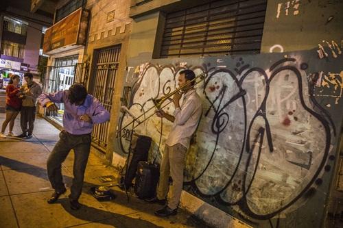 Nghệ sĩ thổi kèn trombone Venezuela Reinaldo Lopez biểu diễn trên một con đường gần chợ Magdalena, Lima. Ảnh: WSJ.