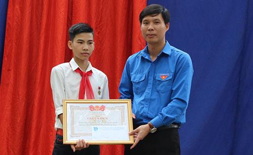 Phó bí thư Tỉnh đoàn Thanh HoáNguyễn Hữu Tuất trao huy hiệu Tuổi trẻ dũng cảm và giấy khen cho nam sinh Vũ Văn Hùng. Ảnh: Lam Sơn.