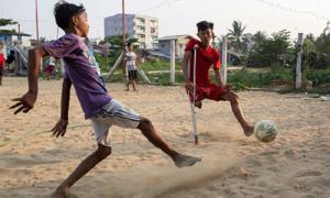Cậu bé khuyết tật Myanmar chống nạng chơi bóng
